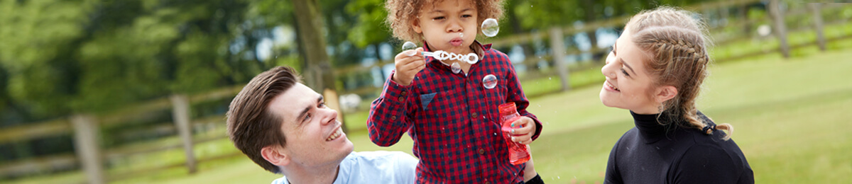 Portrait of funny lovely little boy blowing soap bubbles with foster parents
