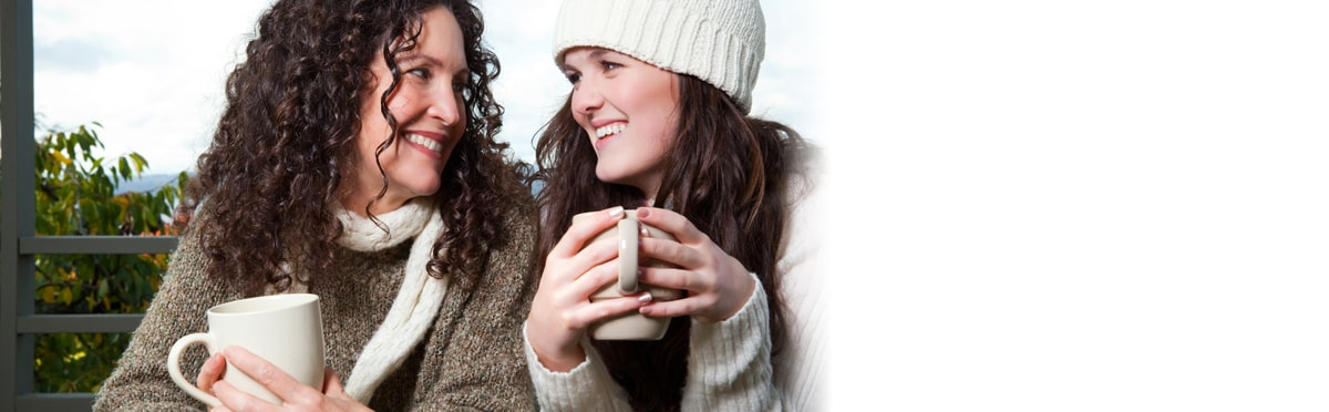 A portrait of a happy foster carer and teen girl drinking coffee outdoor
